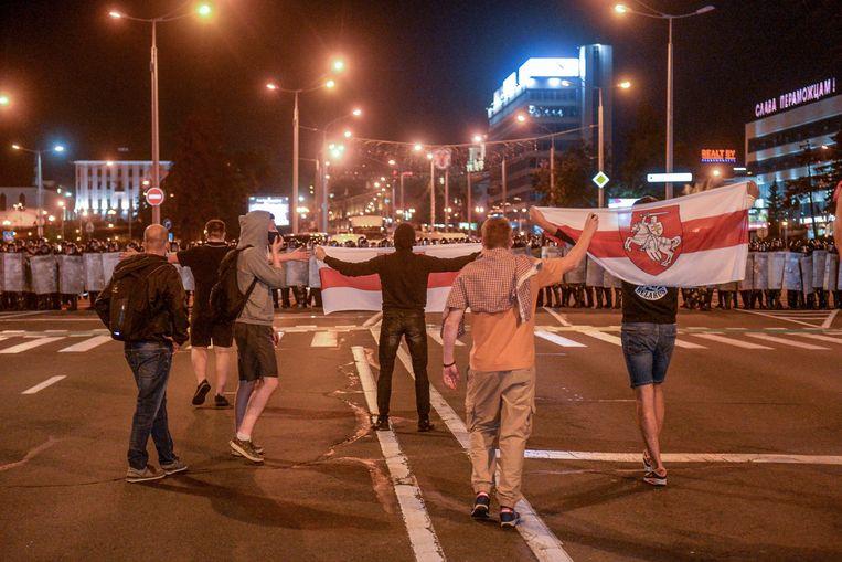 Demonstranten trotseren de politie tijdens het protest in Minsk. Beeld EPA