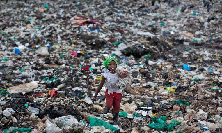 Een achtjarig meisje loopt in 2015, voordat het plasticzakkenverbod van kracht werd, over een vuilstortplaats bij de Keniaanse hoofdstad Nairobi. Beeld AP