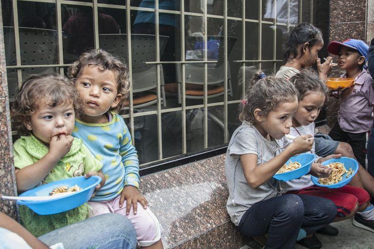 Venezuelan children heat food distributed from Volunteers in Caracas, Venezuela. Beeld Photo News