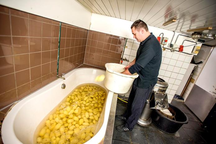 Roel Janssens vult de badkuip met schone aardappelen. Foto Jan van Eijndhoven