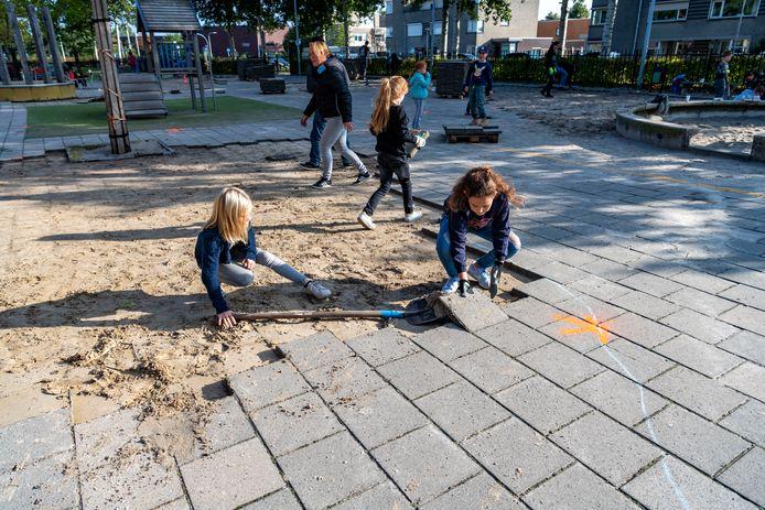 Basisschool Boemerang Tilburg. Isa van der Hoorn met schep, en Tess van Hest met steen in haar hand.
