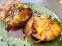 Gefrituurde plakken aubergine in een krokant jasje van tempura-beslag, overgoten met een zoete siroop van sherry.