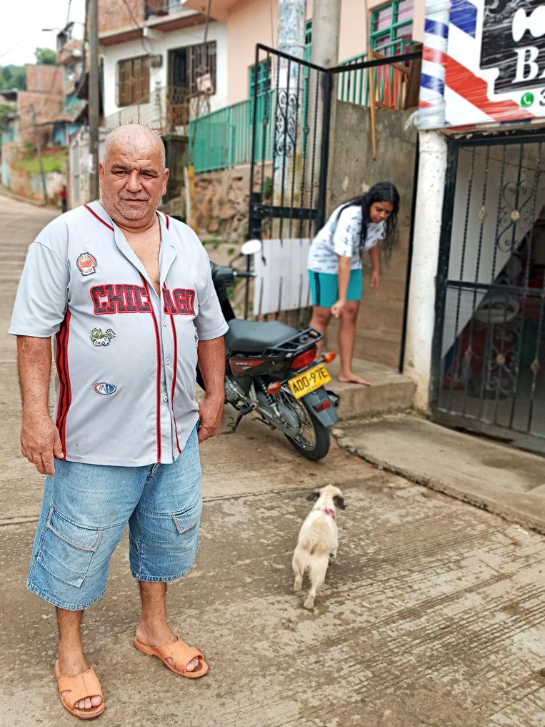 Héctor de Jesús Arcila voor zijn huis in buitenwijk Siloe, in de Colombiaanse stad Cali. Achter hem hondje Lulu en dochter Mayra. Beeld Joost de Vries