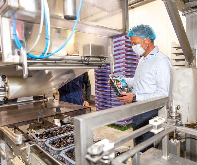 Bij Aquamossel-Triton in Yerseke is de recyclebare verpakkingsfolie van verpakkingsspecialist Weststrate uit Middelburg met succes beproefd. Jasja de Bree, sales manager van Weststrate, controleert de nieuwe mosselbak. Medewerker Kevin Krijger, verscholen achter de inpaklijn, heeft de proef mede begeleid.