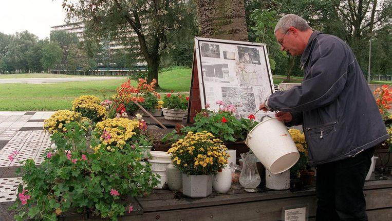 Een buurtbewoner geeft vijf jaar na de ramp de bloemen bij het herdenkingsmonument water. Beeld anp