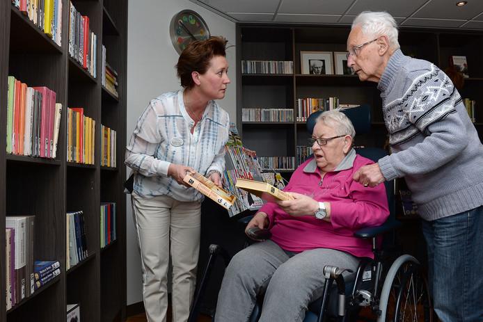 De nieuwe bieb in Madeleine. Riek en Piet de Vries zijn de eerste klanten. Riek leest graag boeken, maar dan wel met grote letters. Jeanette Langen, coördinator informele zorg van Madeleine, helpt haar.