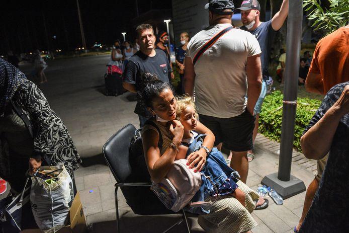 Mensen in de wachtrij om geëvacueerd te worden via boot.