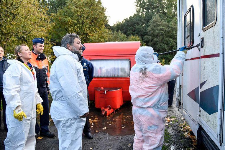 Milieuschepen François De Bleser (midden) kijkt toe hoe een met afval gevulde trailer wordt leeggemaakt.