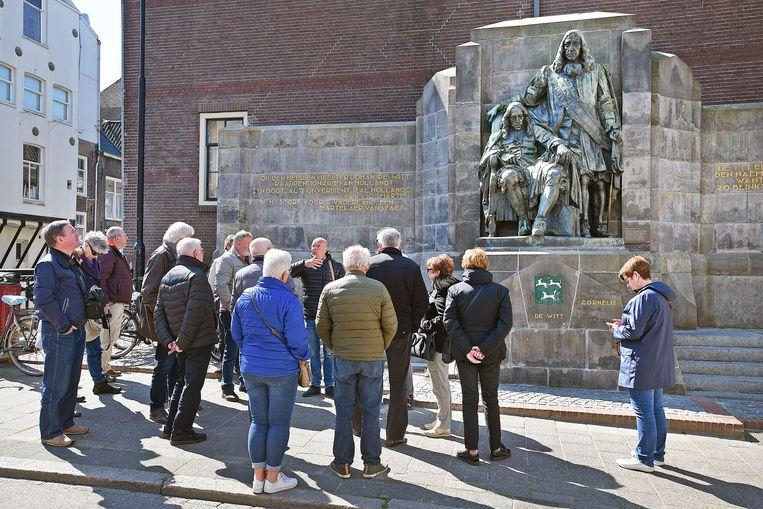 Nederlandse toeristen laten zich door een gids bijpraten over de Dordtse geschiedenis bij het beeld van de Gebroeders de Witt.  Beeld Foto Guus Dubbelman / de Volkskrant