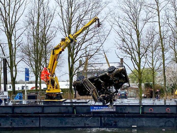 Een van de twee auto's die uit de sloot wordt getakeld in Helmond.