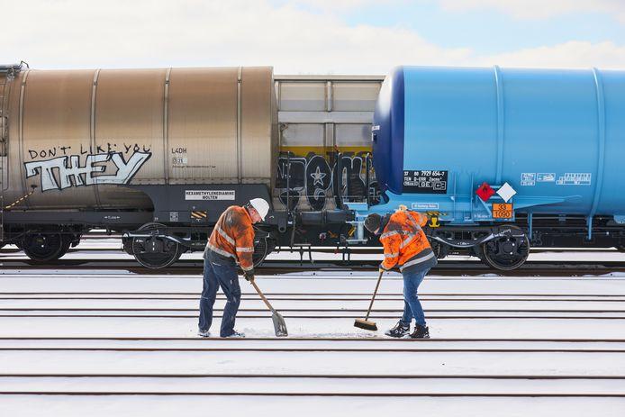 Mensen van spoorbeheerder ProRail maken de rails sneeuwvrij in het Rotterdamse havengebied
