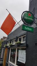 Bij café Sebes in Dordrecht hangt een oranje vlag halfstok.