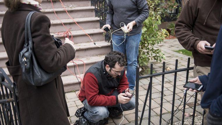 Inwoners van Hoboken in New Jersey laden hun gsm's op bij een huis dat nog stroom heeft. Beeld AFP