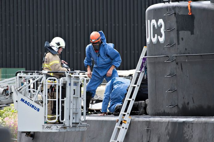 Technici van de politie doorzoeken de geborgen duikboot.
