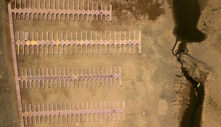 Kajakkers navigeren door een smal deel van het door droogte geteisterde Folsom Lake in Californië. In dit Browns Ravine Cove-gebied van het meer liggen de aanlegsteigers op het droge. Gouverneur van Californië Gavin Newsom heeft voor het grootste deel van de staat een droogtenoodtoestand uitgeroepen.  Beeld AP