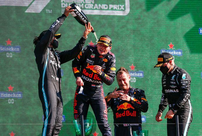 Lewis Hamilton giet op het podium champagne in de nek van Max Verstappen.