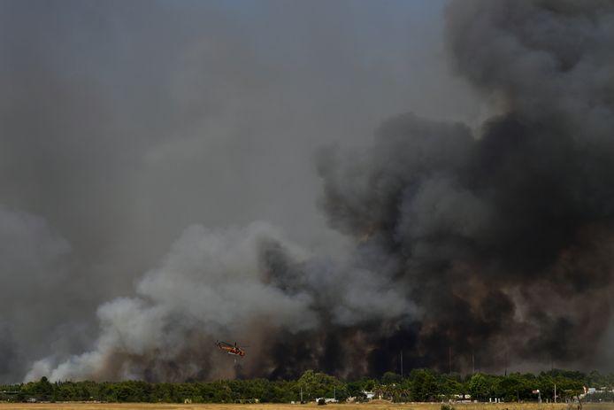 Un hélicoptère des services d'incendie grecs vole au-dessus d'un incendie de forêt qui s'est déclaré à Tatoi, au nord d'Athènes, en Grèce, le mardi 3 août 2021.
