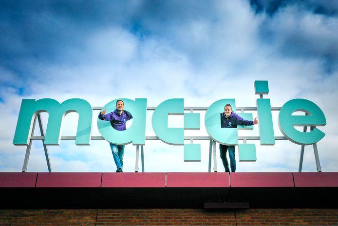 Ceo Pieter Leenman (links) en directeur Martijn den Besten bij het logo van Maqqie op het dak van hun kantoor langs de A15 in Sliedrecht.
