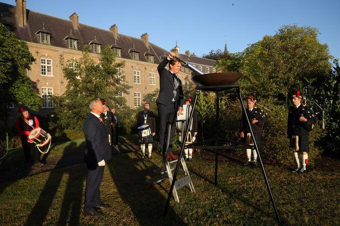 Burgemeester Michel van Veen ontsteekt het vuur in de vuurschaal bij het Vredesmaagd-monument op het Ridderplein in Gemert.