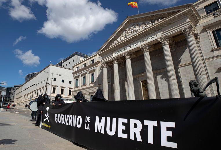 Bij het Spaanse parlement in Madrid werd donderdag gedemonstreerd tegen euthanasie. Elders lieten ook voorstanders zich niet onbetuigd. Beeld AP