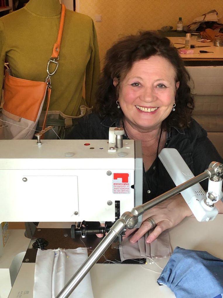 Brigitte Schapendonk maakt thuis achter de naaimachine mondkapjes. Beeld -