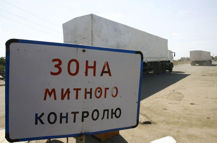 Russische vrachtwagens steken de grens met Oekraïne over bij het Izvarino checkpoint. Beeld afp
