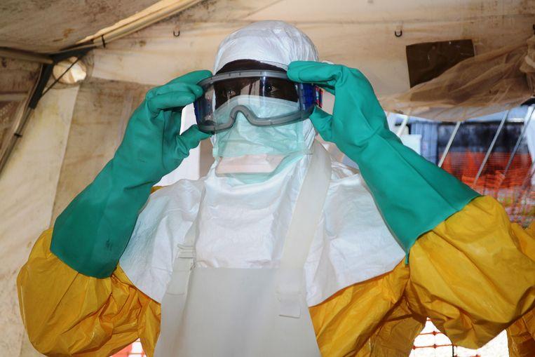 Een medewerkers van Artsen zonder Grenzen trekt beschermend materiaal aan in een ziekenhuis in Conakry, waar patiënten met ebola worden behandeld.  Beeld AFP