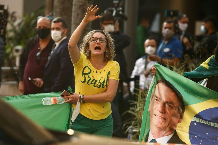 Een aanhanger van Bolsonaro bij de ingang van het ziekenhuis waar de president is opgenoemen. (16/07/2021) Beeld REUTERS