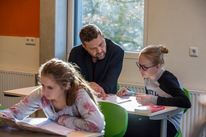 Steeds meer kinderen krijgen huiswerkbegeleiding. Onder andere op het Zuidwesthoek College. Huiswerkbegeleider Olaf Kleine Schaars (midden) begeleidt Nina (rechts achter) en Xina (links voor) met huiswerk.
