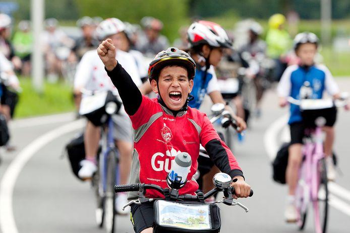 De bontgekleurde stoet van fietsers en begeleiders van Ome Joop's Tour, voorafgegaan door vier politiemotoren, zich langs de Zutphenseweg richting Lochem.