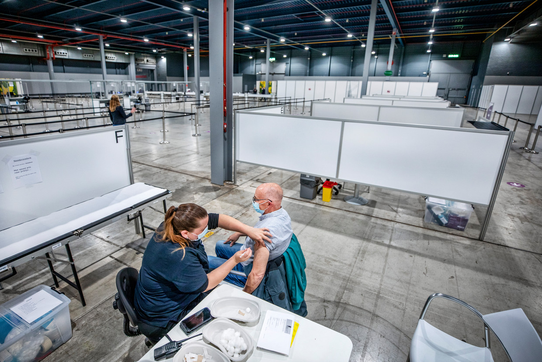 Frank Broers (69) wordt gevaccineerd in de grote maar ook lege priklokatie van de GGD in de Jaarbeurs in Utrecht, die woensdagavond is opengegaan.  Beeld Raymond Rutting / de Volkskrant