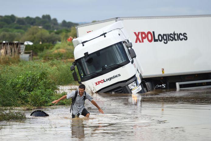Un homme marche devant un camion bloqué dans une route inondée à Codognan, dans le département du Gard, en région Occitanie, dans le sud de la France, le 14 septembre 2021 suite à de fortes pluies.
