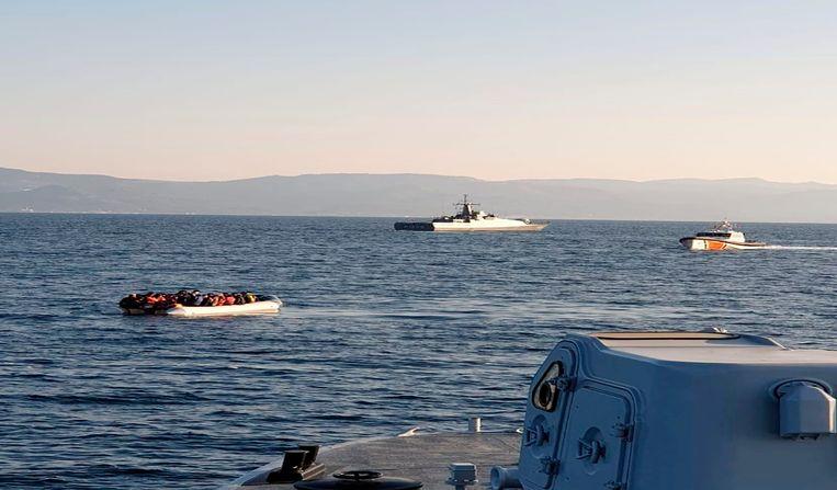 Een bootje met migranten, links, tussen de Turkse kust en het Griekse eiland Lesbos. Foto van de Griekse kustwacht, op de achtergrond een schip van de Turkse kustwacht. Beeld AP