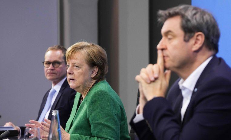 De Duitse bondskanselier Angela Merkel (midden), de premier van Beieren (rechts) Markus Soeder en de burgemeester van Berlijn Michael Mueller tijdens de persconferentie. Beeld AFP