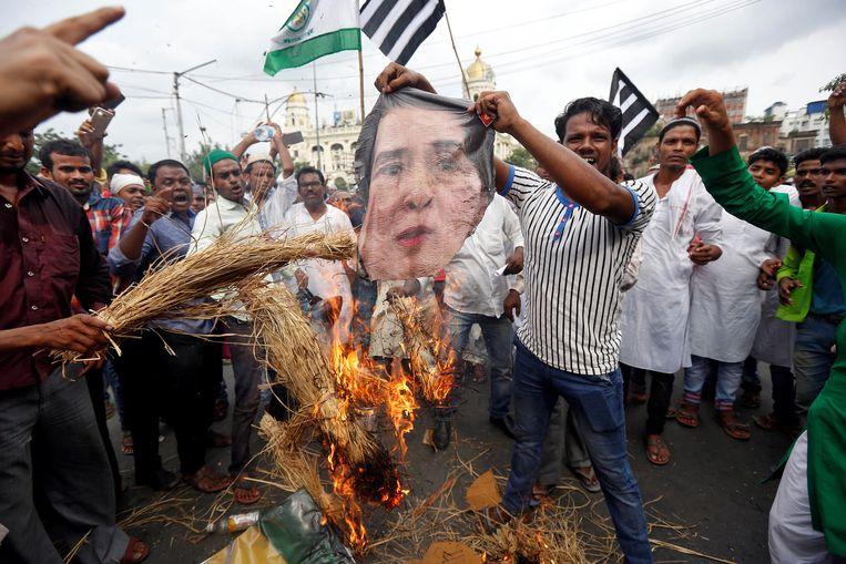 Bij een protest in India wordt de beeltenis van Aung San Suu Kyi verbrand. Beeld REUTERS