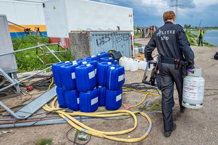 Een medewerker van een speciaal politieteam onderzoekt het drugslab dat werd gevonden aan de Scherpekamp bij Angeren.