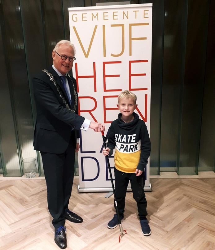 Maas van Bree (8) neemt een prikstok in ontvangst van de burgemeester