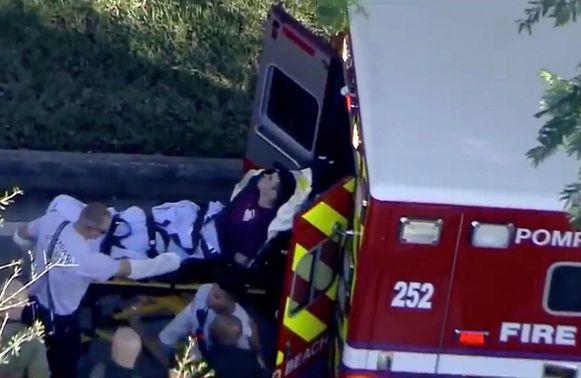 De verdachte wordt in een ambulance gelegd.