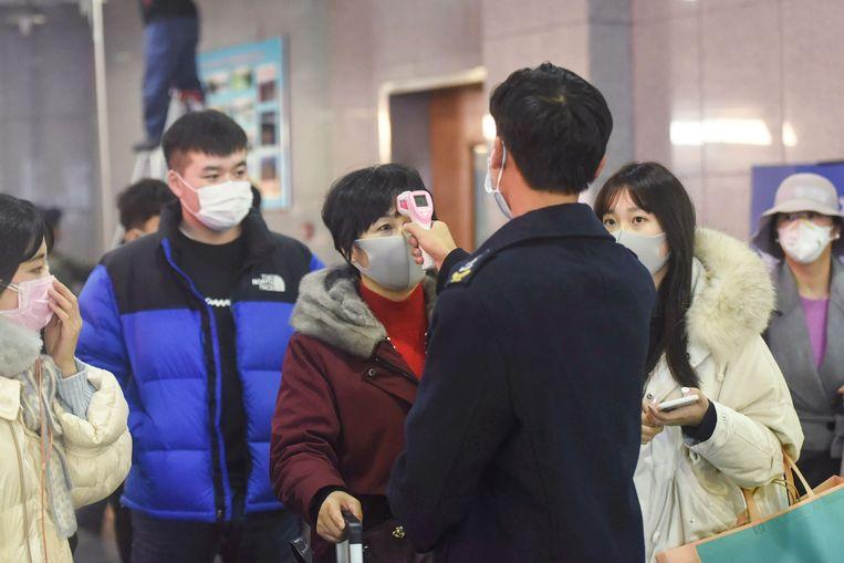 De temperatuur van passagiers uit Wuhan wordt na een treinrit gecontroleerd.