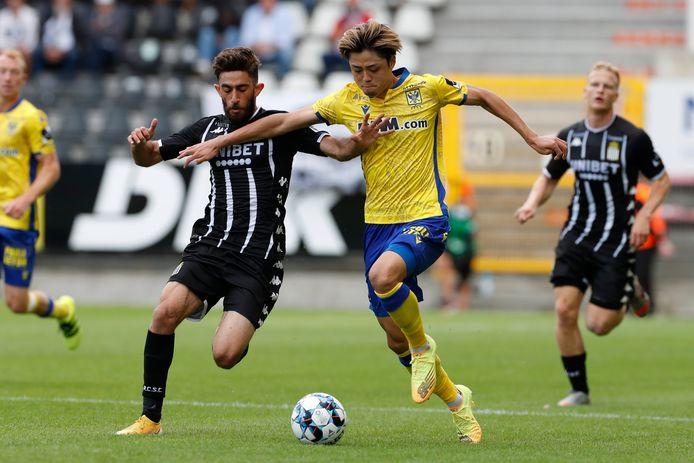 Ko Matsubara van Sint-Truiden op de hielen gezeten door Ali Gholizadeh van Sporting Charleroi.