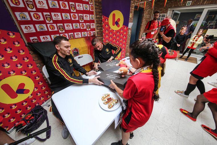 Dit meisje overhandigt de voetballers een Belgium Beer Box en eclairs.