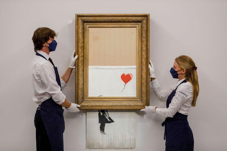 Het kunstwerk 'Girl with Balloon', dat na veiling voor de helft door een versnipperaar ging.  Beeld AP