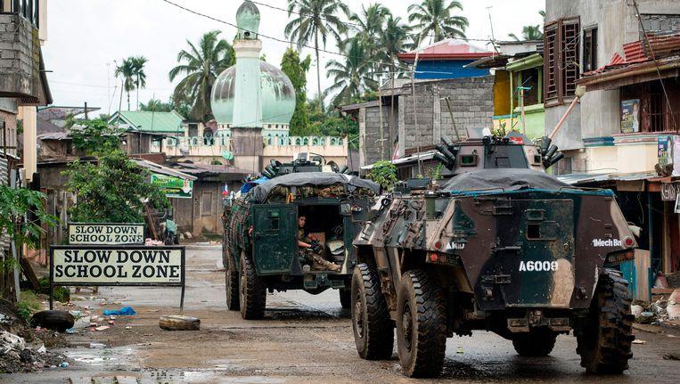 Filipijnse troepen rijden in pantservoertuigen door de stad Marawi op Mindanao. Beeld AFP