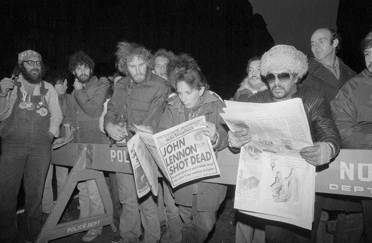 Menigtes verzamelen zich voor het appartementencomplex Dakota in New York waar John Lennon werd doodgeschoten.   Beeld Bettmann Archive