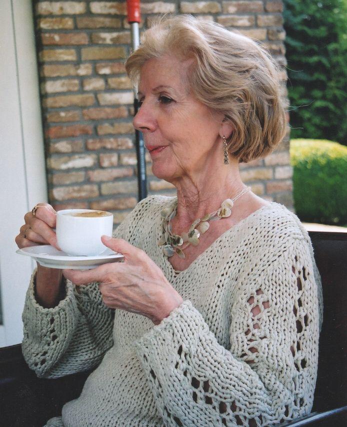 Margriet Dinkelaar genietend van een kopje koffie in de tuin op het terras.