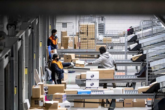 Medewerkers van post- en pakketbezorger PostNL sorteren pakketjes in het pakkettensorteercentrum.