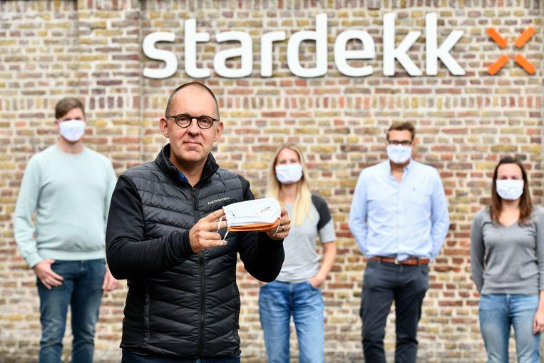 CEO Vincent Goemaere toont het gepersonaliseerde mondmasker dat het bedrijf voor de medewerkers liet maken. Beeld Photo News