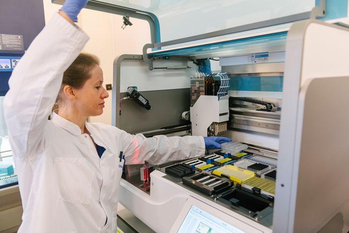 Een laborante plaatst een rekje met proefmonsters van mogelijk met het coronavirus besmette mensen in de machine voor het isoleren van DNA, dit is stap twee van de coronatest.