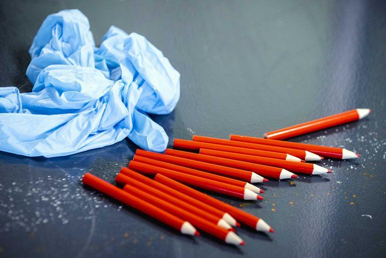 Rode potloden en wegwerphandschoentjes in een model-stembureau in Rotterdam Charlois. Iedereen die een stem uit gaat brengen krijgt een eigen potlood. Voor de Tweede Kamerverkiezingen moeten alle stembureaus coronaproof worden ingericht.  Beeld ANP