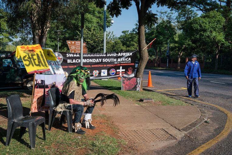 Een voorbijganger werpt een blik op het protest van de organisatie Swart Maandag. Beeld Bram Lammers